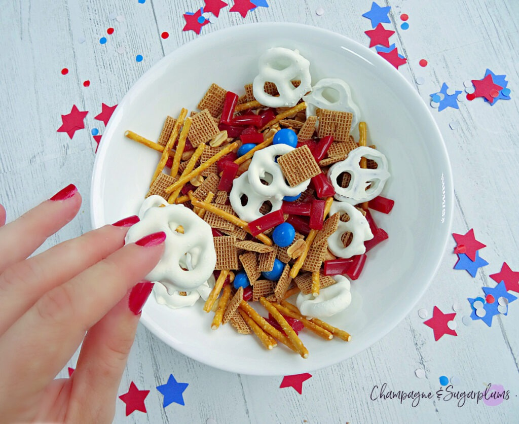 A hand grabbing a yogurt covered pretzel from a bowl of Fourth of July Snack Mix on a white background with blue and red stars and confetti by Champagne and Sugarplums
