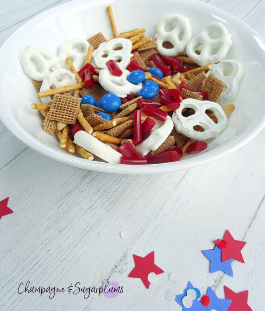 Snack Mix in a white bowl on a white background with blue and red stars and confetti by Champagne and Sugarplums