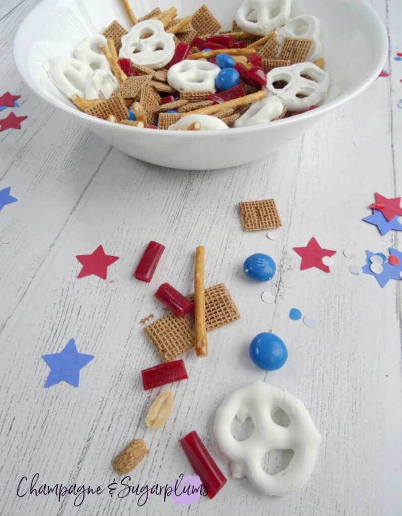 Fourth of July Snack Mix in a white bowl on a white background with blue and red stars and confetti by Champagne and Sugarplums
