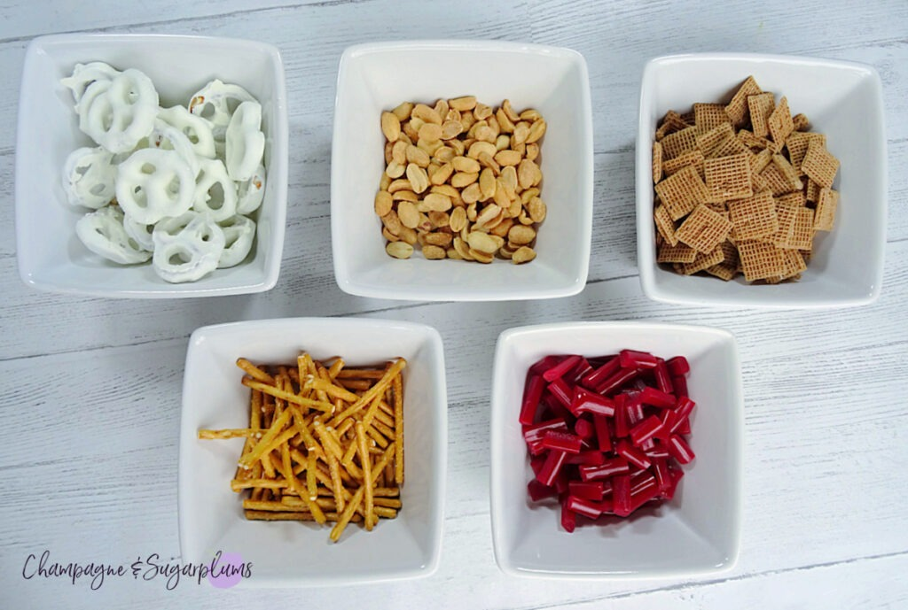 White bowls with ingredients for Snack Mix on a white background by Champagne and Sugarplums