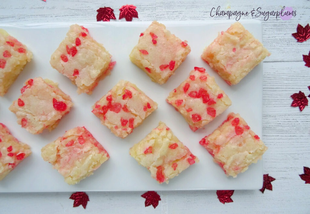 Canada Day Brownies on a white plate with red maple leaf confetti scattered around by Champagne and Sugarplums